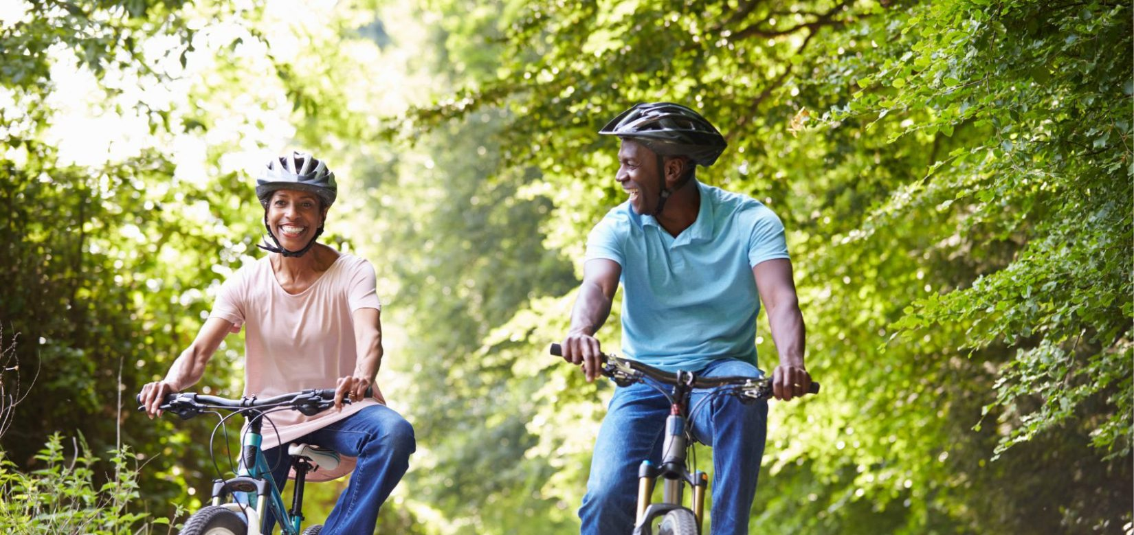 Middle-aged couple smiling while riding bikes on a sunny day