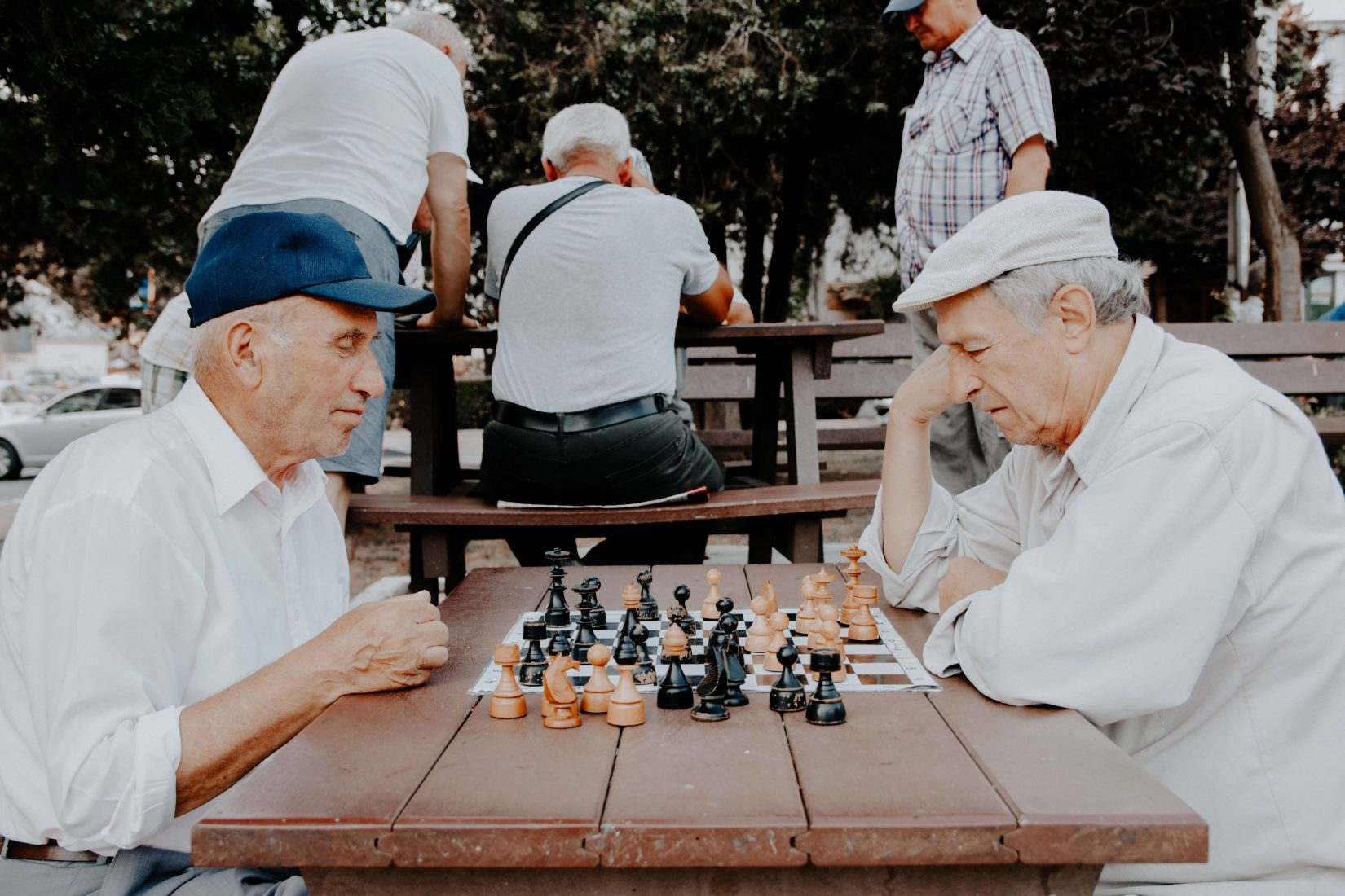 Two older men playing chess in a park at a picnic bench