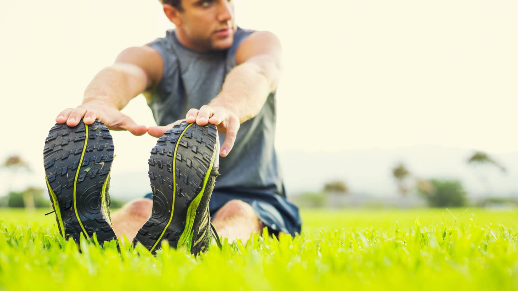 Man in running gear stretching on grass