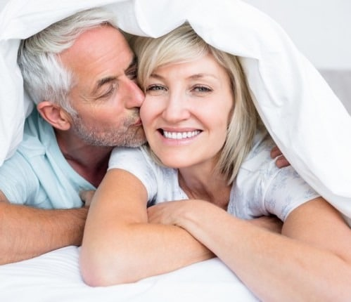 Older man kissing wife on the cheek while she smiles and looks at the camera