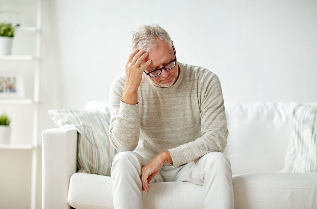 Worried Senior Man Sitting on Couch Thinking About TriMix for Erectile Dysfunction