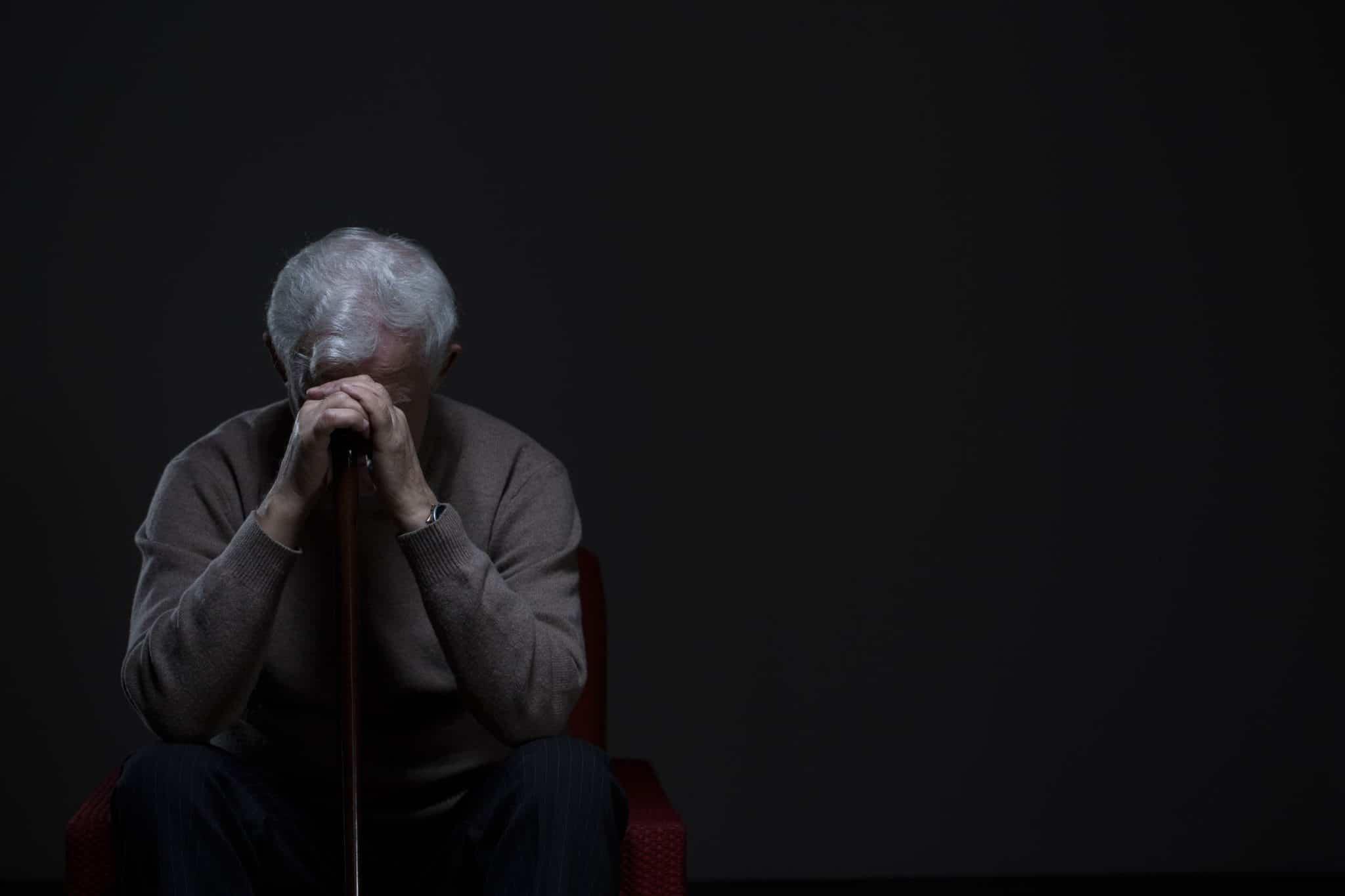 Older Man in Dark with Head in His Hands
