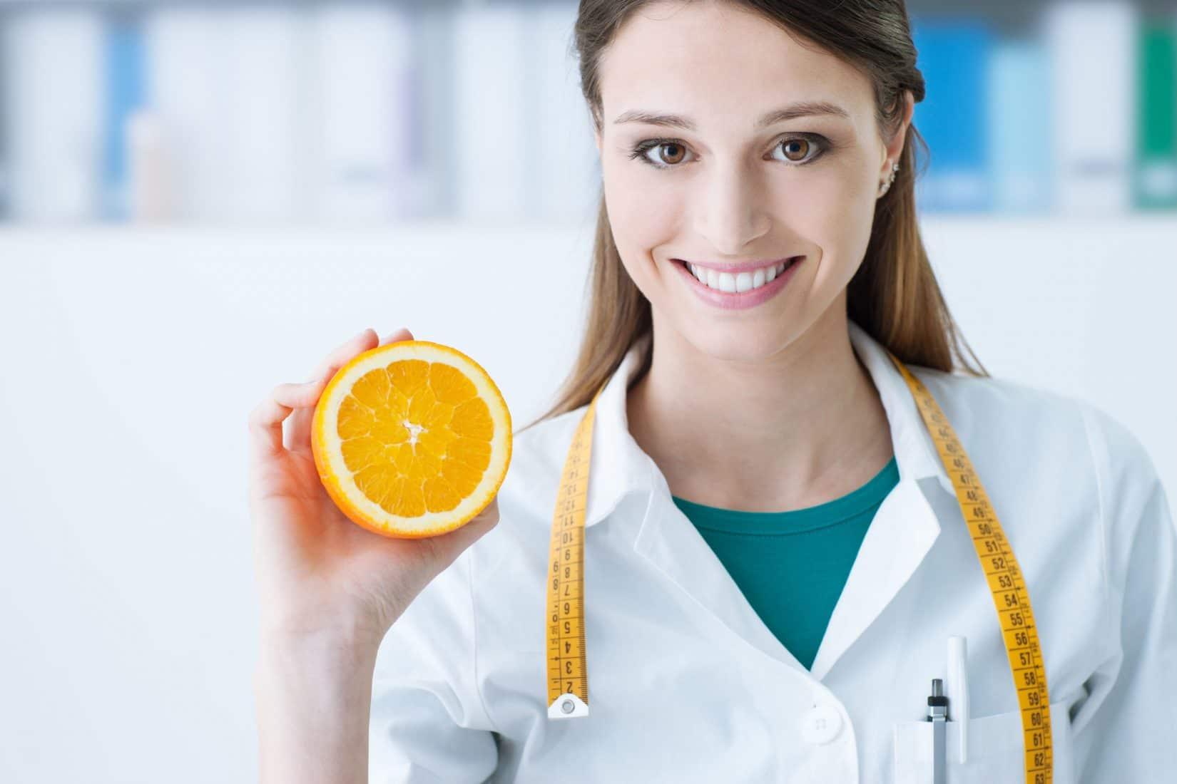 Female Doctor Holding Up Orange