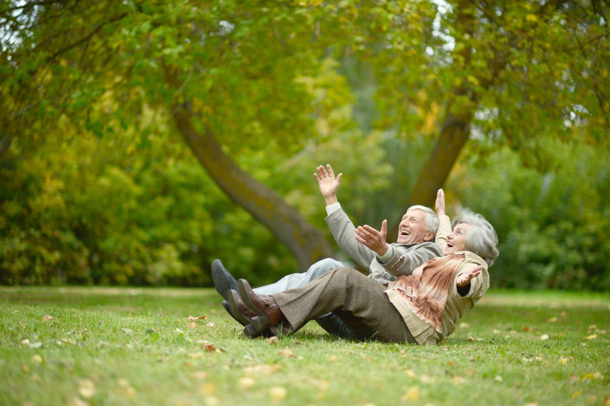 Elderly Couple Playing and Laughing on the Ground at the Park