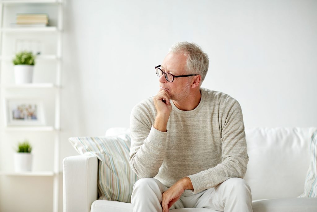 Older Man Sitting on Couch and Thinking