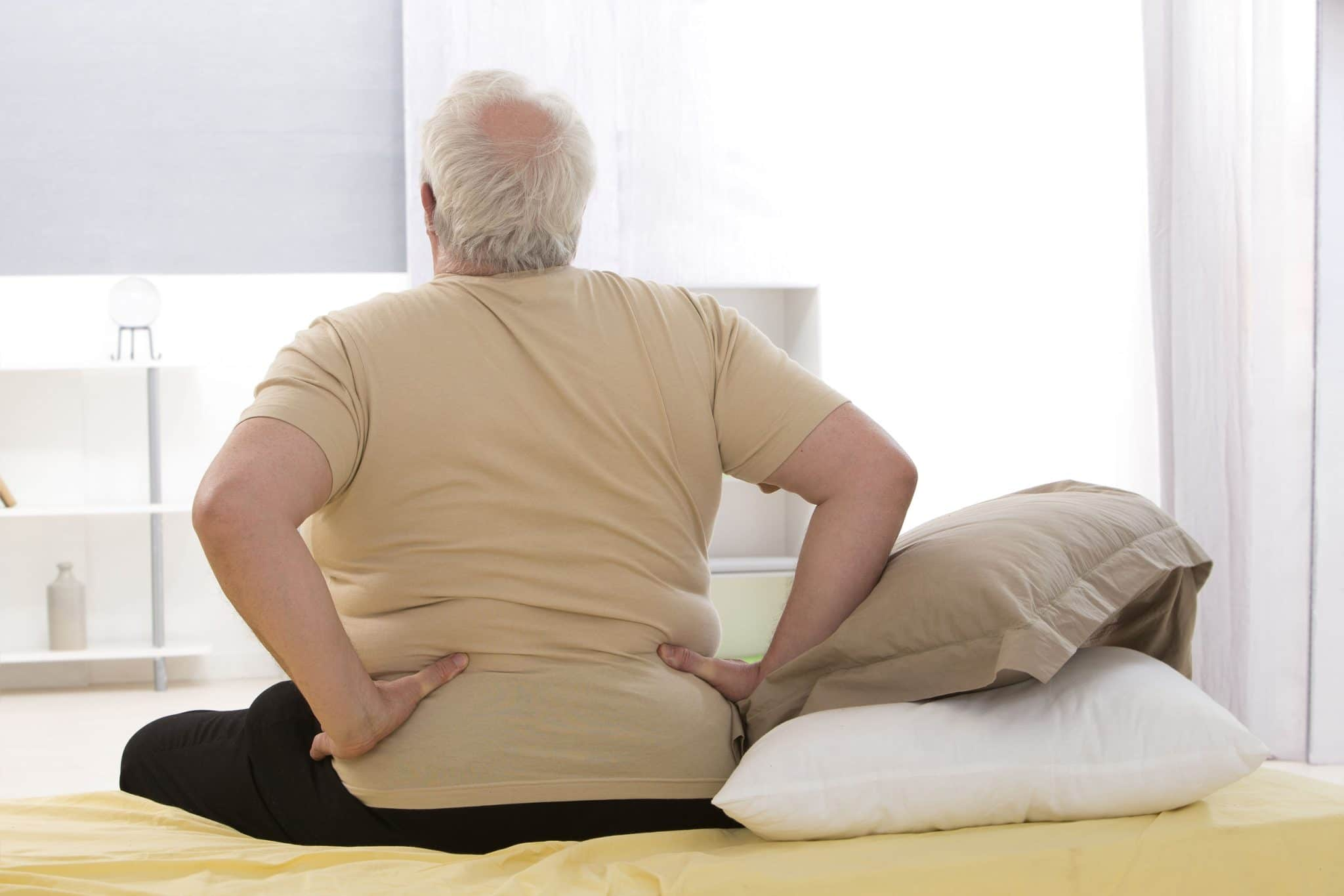 Senior man holding lower back while sitting on the edge of a bed