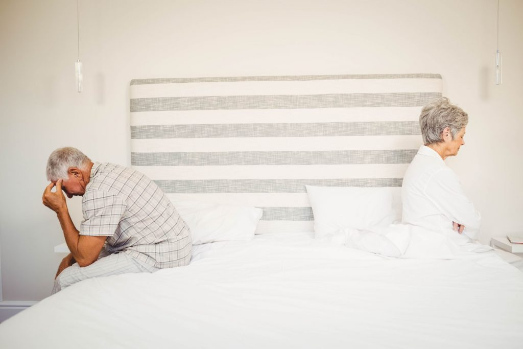 upset senior couple sitting on the opposite ends of the bed after a fight about what causes erectile dysfunction