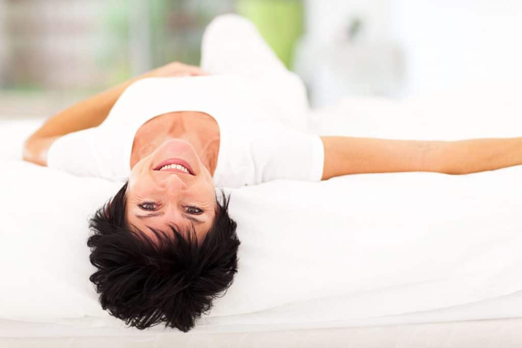 middle-aged woman laying on bed and smiling at camera