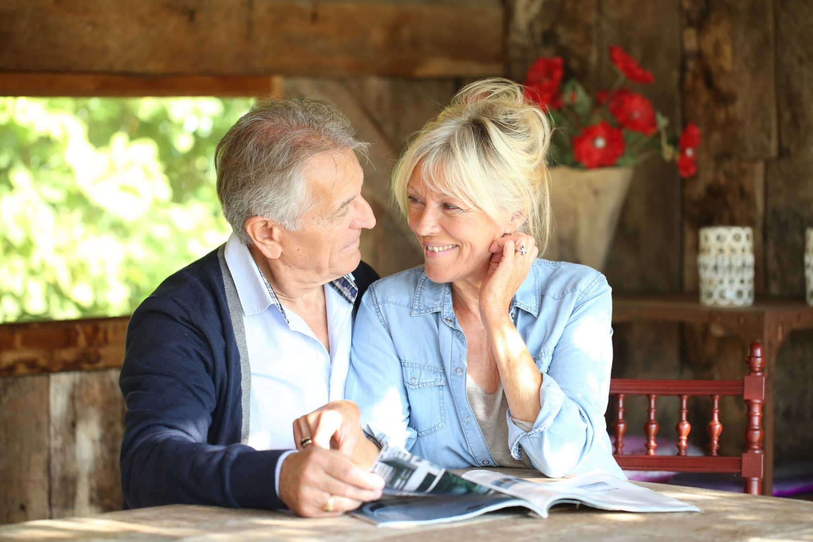 Senior couple in yard reading magazine about ED injections trimix