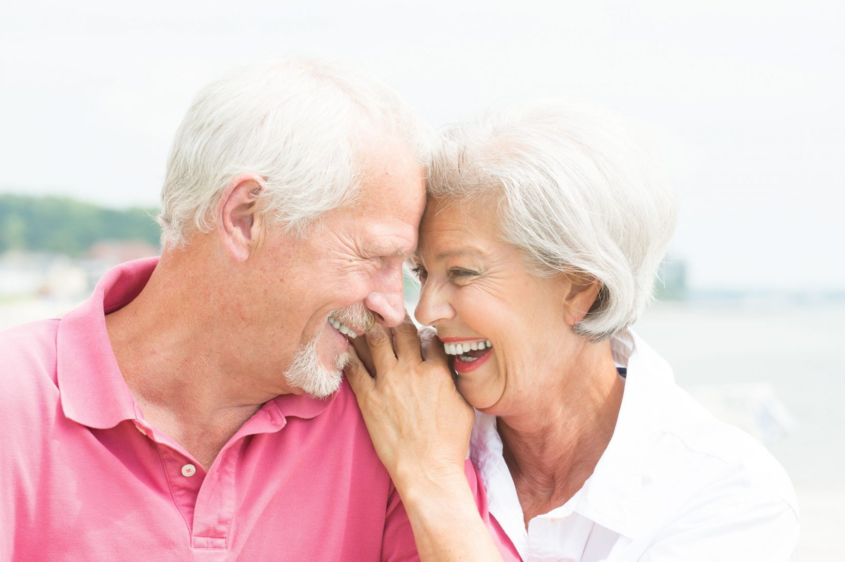 laughing older couple sitting close to each other outside