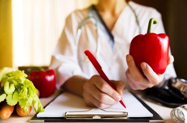 Woman holding up apple whlie writing something with a pen - Medical Weight Loss Program and Prescription Weight Loss Injections