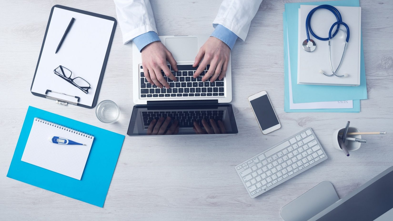 Doctor Typing on Laptop with Paperwork on Desk