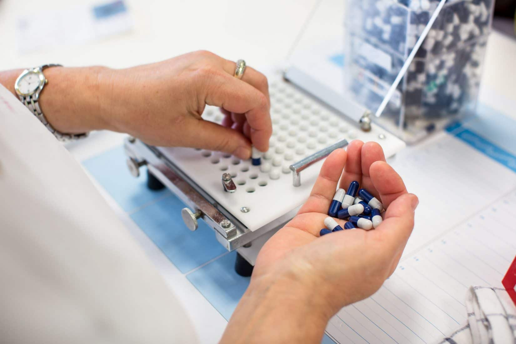 Woman putting pills into a pill counter at a compounding pharmacy