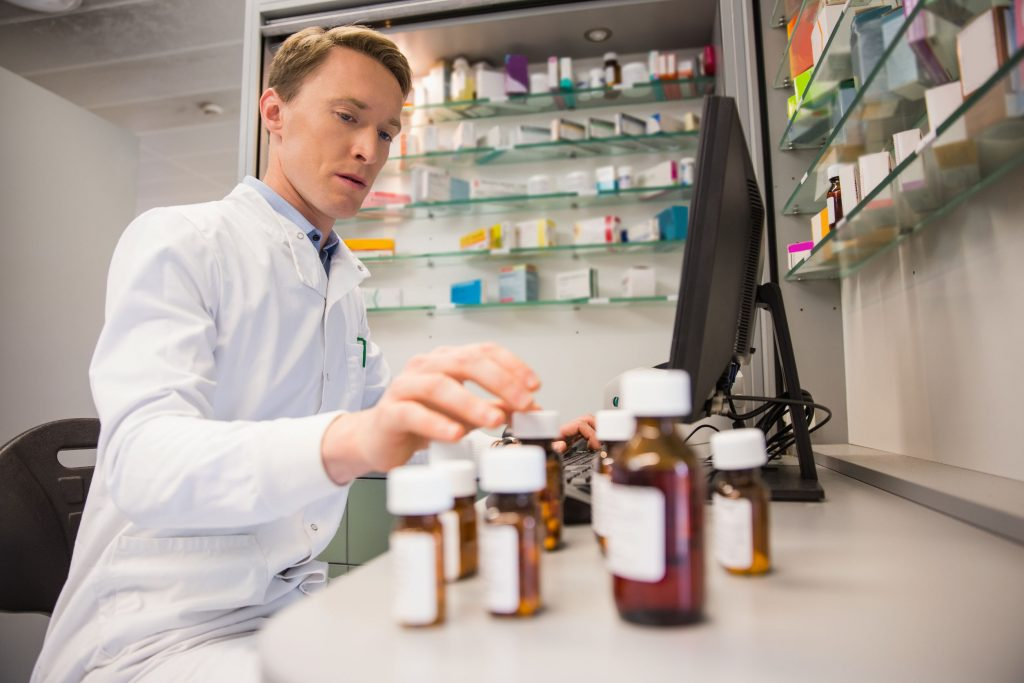 Pharmacist typing in information into computer while looking at medication bottles