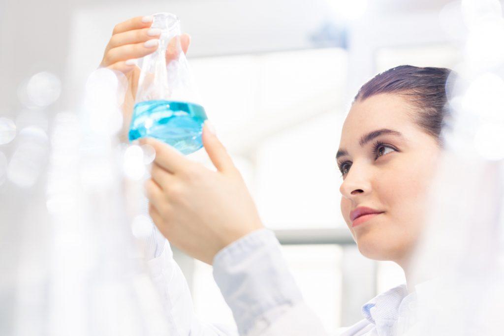 nurse examining a bottle of blue liquid