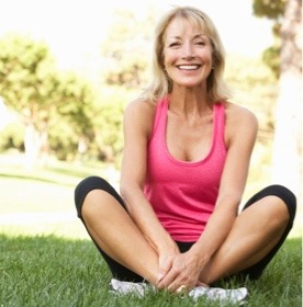 Smiling white woman sitting in gym clothes outside on the grass
