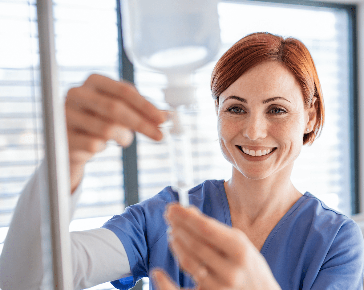 Female Nurse Smiling While Adjusting IV Nutritional Therapy Drip