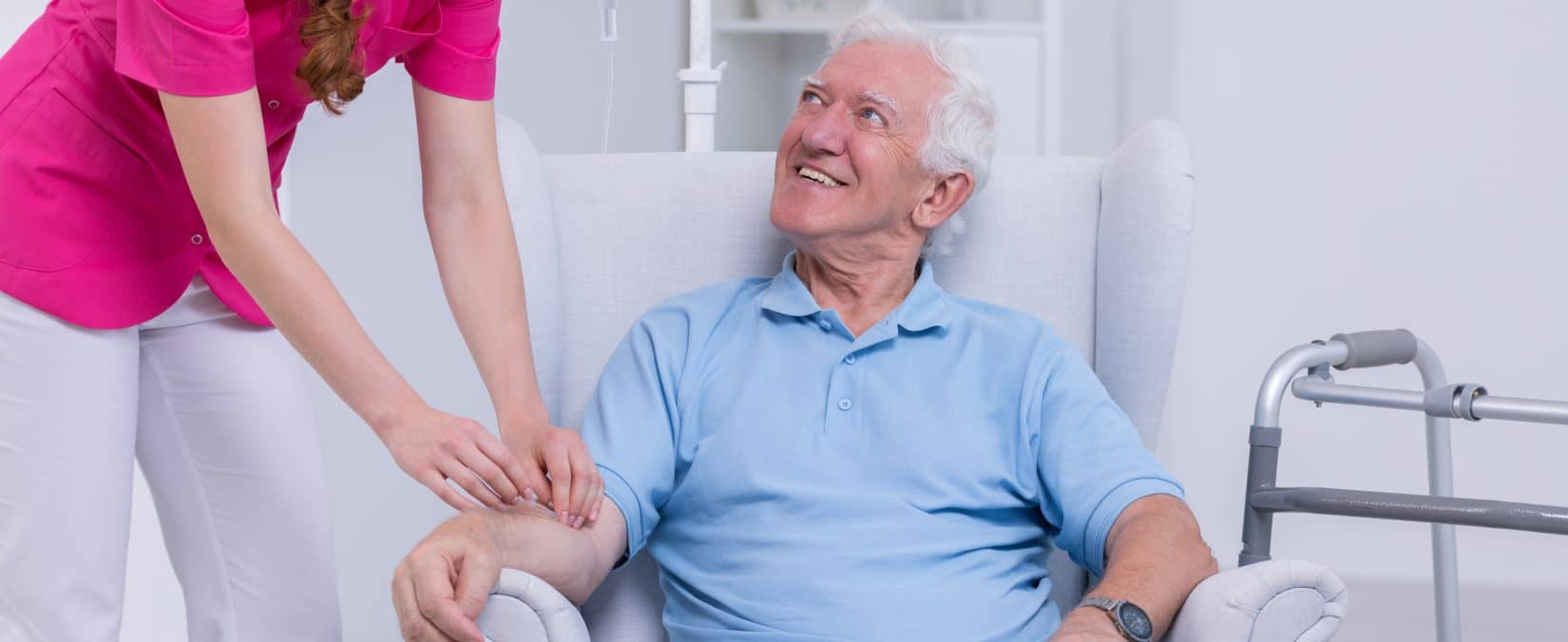 Nurse connecting IV vitamin therapy drip to senior patient