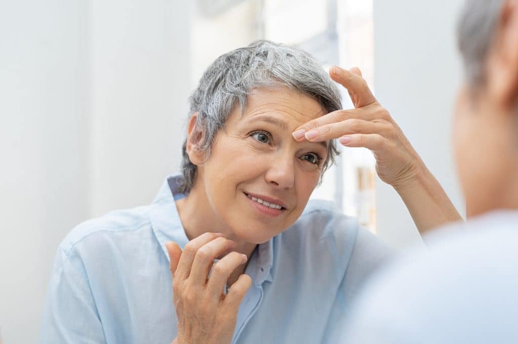 Older woman smiling and looking her face in the bathroom mirror while touching wrinkles on forehead