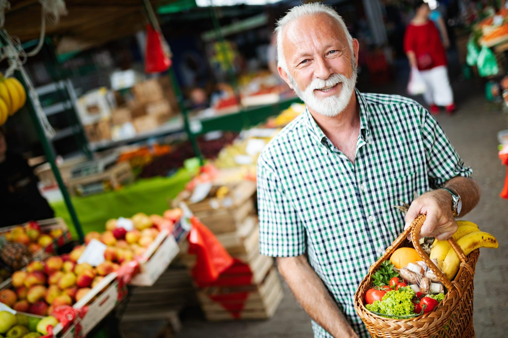 senior man smiling and holding basket of fresh produce while shopping at a market